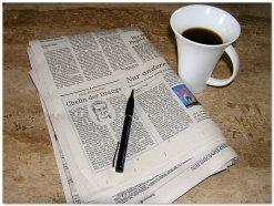 Zeitung, Stift und Kaffeetasse