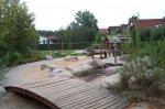 Wasseranlage mit Holzbrücke auf dem Spielplatz Karlsbader Straße