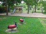 rote Wipptiere und Sandkasten mit Rutsche auf dem Spielplatz Pinienweg