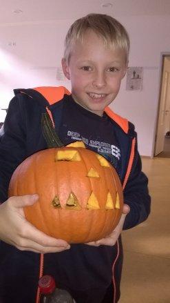 Ein Kind mit einem Halloween-Kürbis