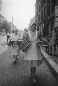 Altes Foto von Damen, die Quetschekuchen verteilen