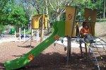 grüne Rutsche mit kleinem Mädchen auf dem Spielplatz Suicardusstraße